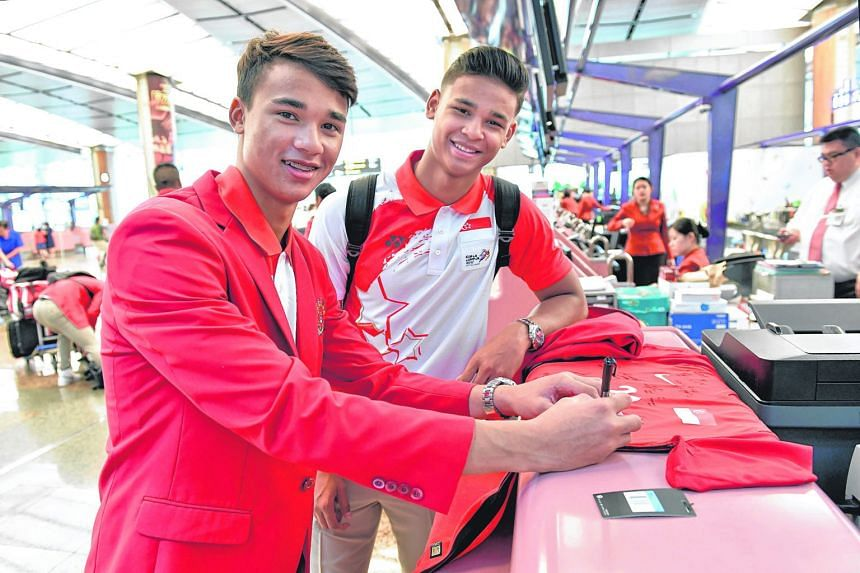 Ikhsan, 18, and Irfan Fandi (right), 20, sons of Singapore football legend Fandi Ahmad, autographing a jersey at Changi Airport before departing for the SEA Games yesterday afternoon. The football squad comprising Under-22 players were among the firs