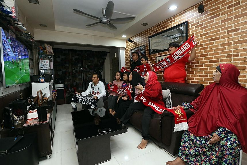 Masliah (second from right) and her family gather to watch Liverpool's Premier League opening match against Watford yesterday. Liverpool fans at the Four Points by Sheraton Singapore cheering after the Reds score against Watford.