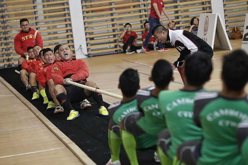 A combined team (in red) from Singapore's Home Team in action against Cambodia during the Asian Tug of War Championships at Republic Polytechnic Sports Hall yesterday. The Singapore team subsequently failed to advance beyond the preliminary round. Th
