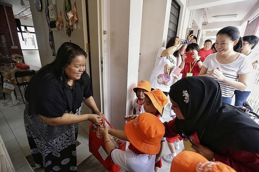 PCF Sparkletots pre-schoolers, accompanied by Tampines GRC MP Cheng Li Hui, giving a bag of provisions to housewife Julianah Sani, 41, yesterday.