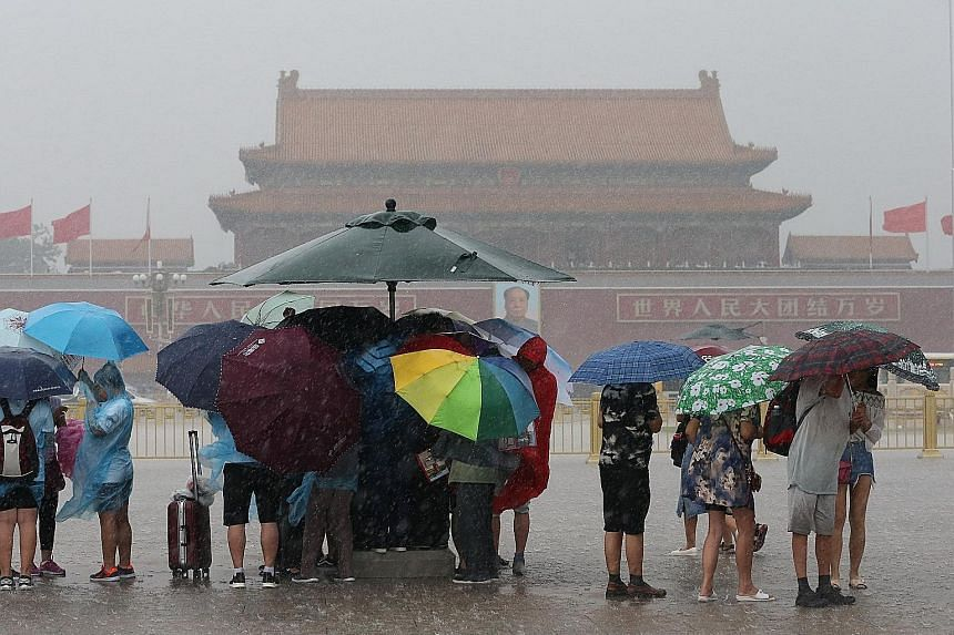 Tourists visiting Tiananmen Square in Beijing yesterday held umbrellas as heavy rain fell. Thunderstorms lashed the Chinese capital yesterday, disrupting hundreds of flights at the city's airport, one of the largest airports in the world. Other airpo