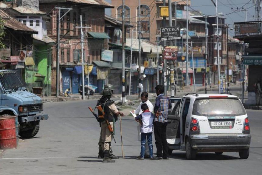 Indian Paramilitary soldiers stop a vehicle near a temporary barricade during restrictions in a downtown area of Srinagar, the summer capital of Indian Kashmir on August 12, 2017.