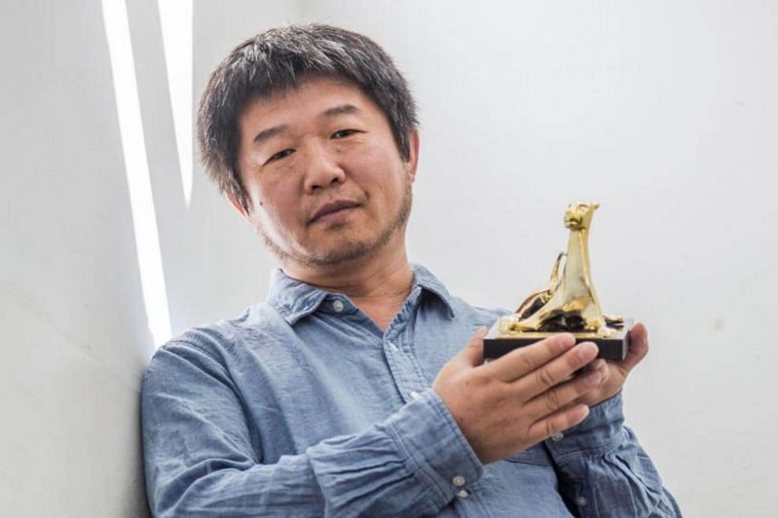 A handout picture released on August 12, 2017 by the Locarno International Film Festival shows Chinese director Wang Bing posing with the Golden Leopard (Pardo d'oro) trophy.