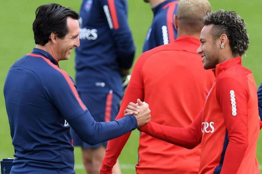 Neymar (right) shaking hands with Paris Saint-Germain head coach Unai Emery during a training session near Paris on Aug 11, 2017.