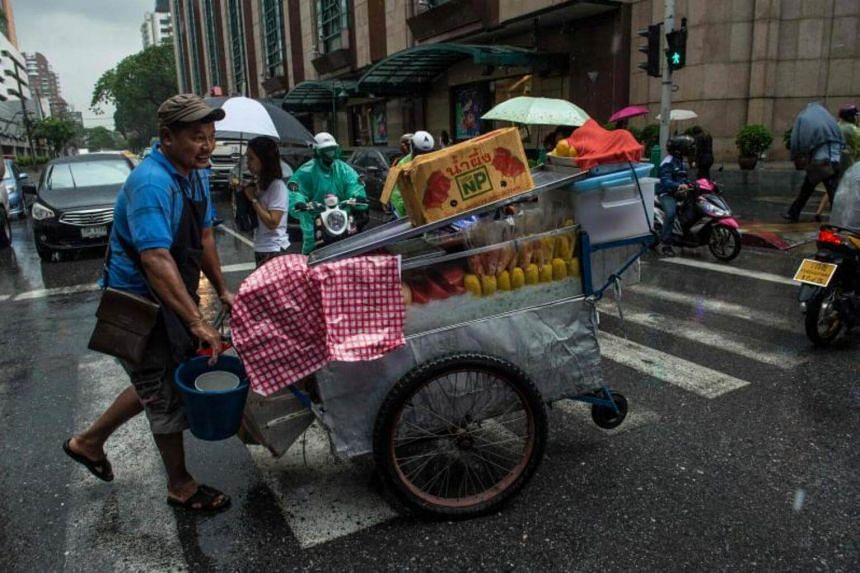 A fruit street vendor pushes a cart with food in a rainy morning at an intersection in Bangkok on May 17, 2017.