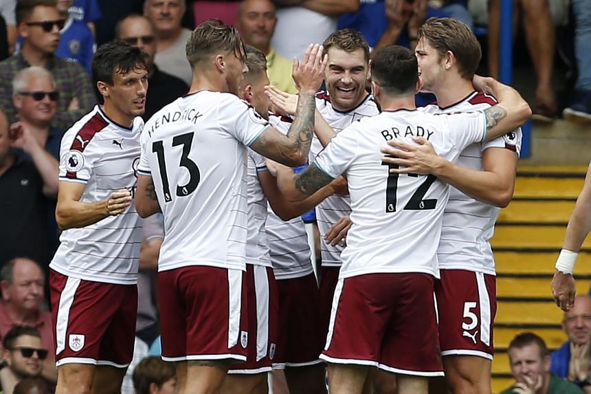Burnley's Welsh striker Sam Vokes (centre) celebrates with teammates after scoring the opening goal.