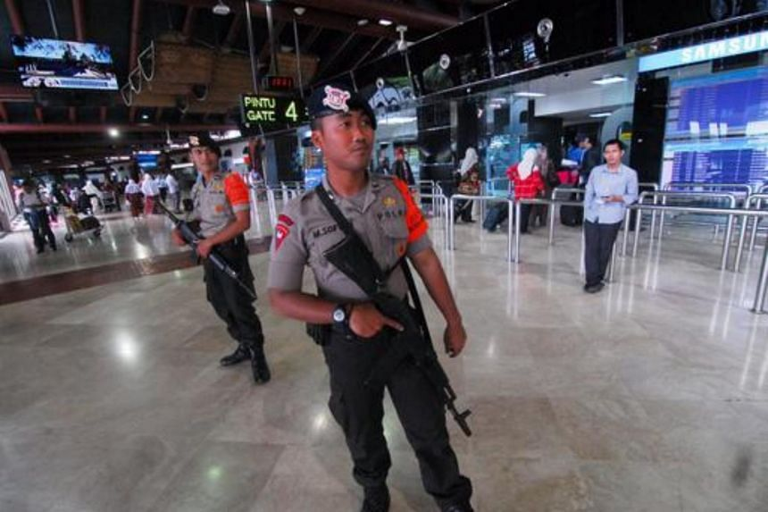 Indonesian police officers stand guard inside a terminal building of the Soekarno-Hatta international airport in Jakarta, Indonesia, on Feb 25, 2016.