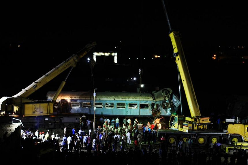 Egyptian workers and security personnel prepare to retrieve the wreckage left by the collision of two passenger trains in Alexandria, Egypt, on Aug 11, 2017.