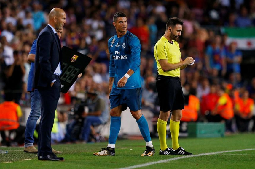 Real Madrid's Cristiano Ronaldo walks off dejected past coach Zinedine Zidane after being sent off, on Aug 13, 2017.