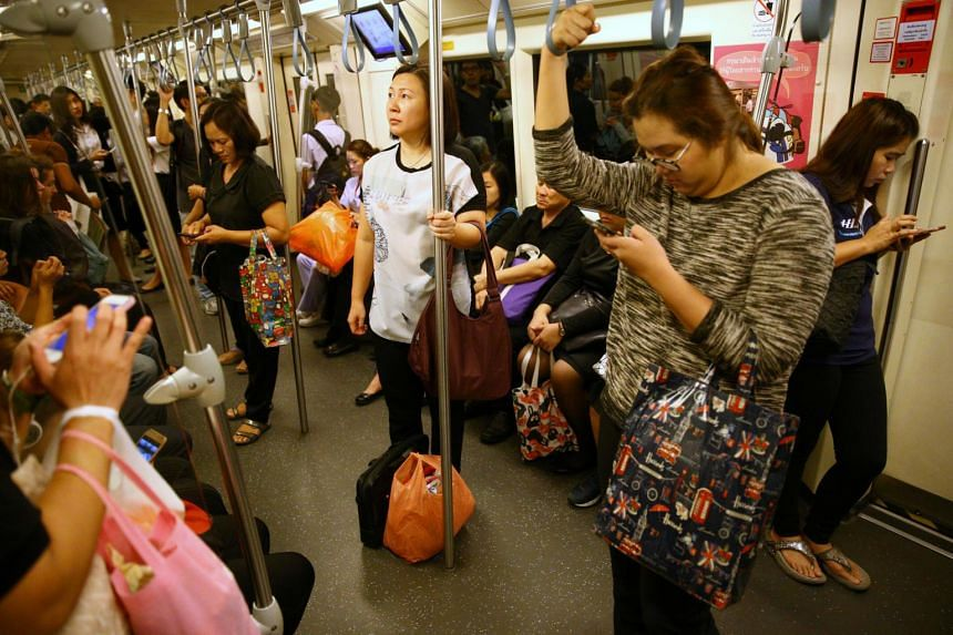 Passengers using their mobile phones as they ride a train in Bangkok, Thailand, on June 12, 2017.