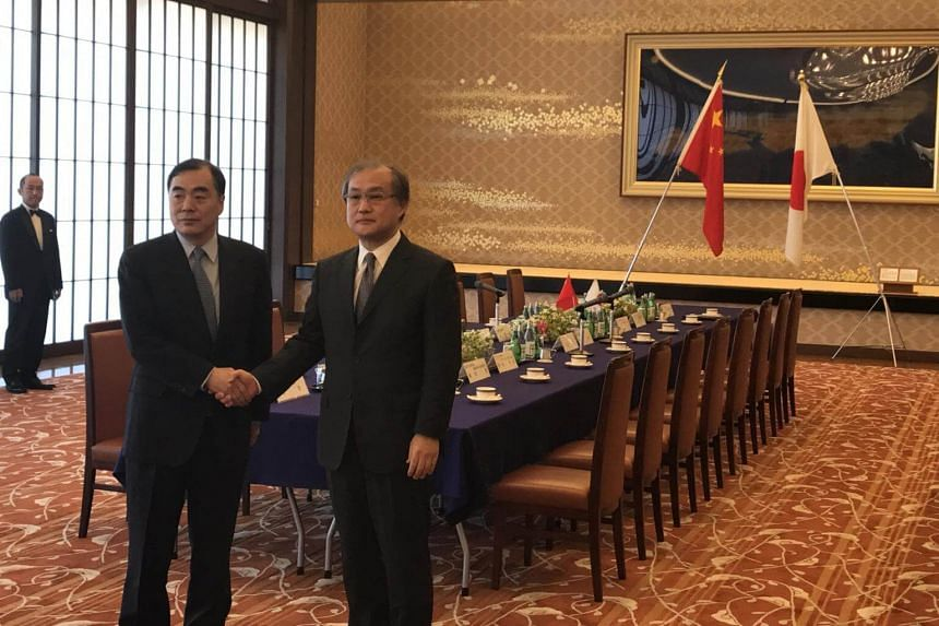 Chinese assistant foreign minister Kong Xuanyou (left) shake hands with Japanese deputy foreign minister for political affairs Takeo Akiba before their meeting at the Iikura Guest House in Tokyo on April 4, 2017.