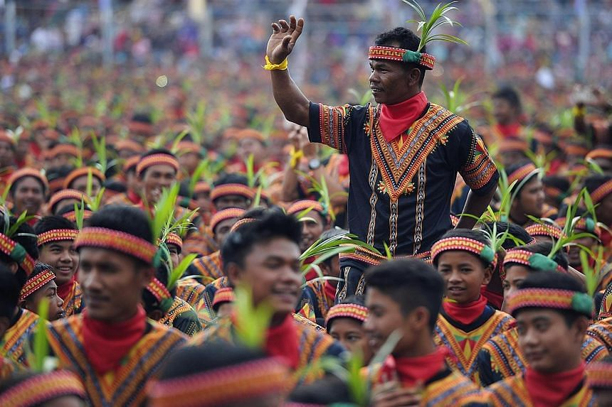 Men clad in elaborate traditional costumes at yesterday's event, which was aimed at attracting more visitors to the Indonesian province.