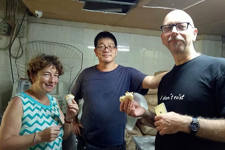 Above: Swiss tourists Gisela Aeschbach and Fredy Diener at Jie Bakery, with owner Jimmy Mah, as part of Tribe's Disappearing Trades tour. Right: Tribe co-founder Jason Loe with Mr Mah, who enjoys opening up his bakery to visitors as he has many stori