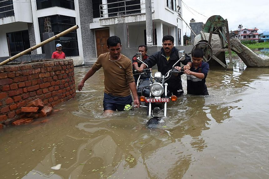 A flooded street in Patan, near Kathmandu, yesterday. Rescuers are searching for scores buried in submerged villages as thousands flee for higher ground.