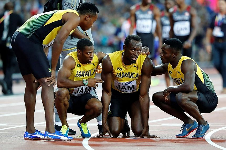 Jamaican star Usain Bolt is comforted by his teammates after suffering a hamstring injury during the 4x100m relay final - his swansong race.