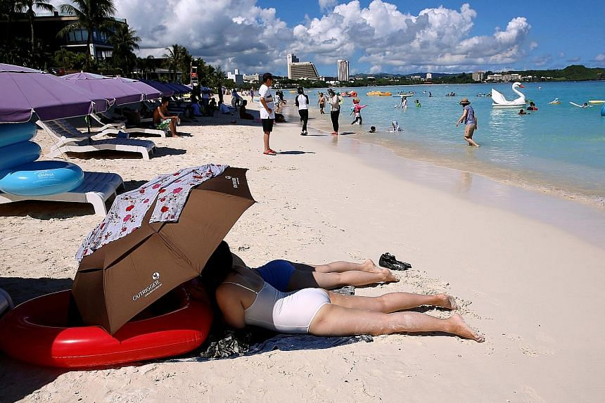 Left: Tourists sunbathing in the Tumon district on the island of Guam, a US Pacific territory, last Saturday. Some 85 per cent of its tourists come from South Korea and Japan. Above: Guam Governor Eddie Calvo speaking to the media at the government c