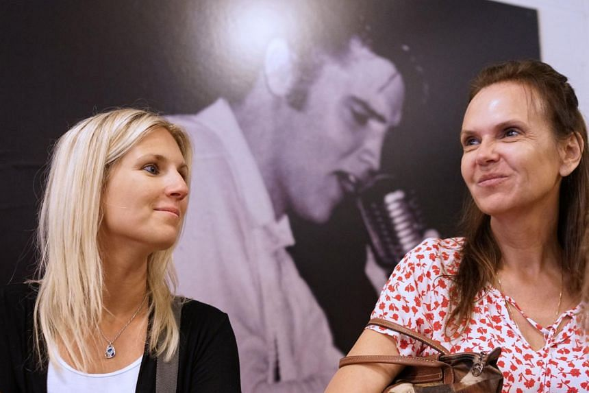 Two fans are seen in front of a photo of Elvis Presley during a tour of Sun Studio, in Memphis, Tennessee, on Aug 13, 2017.