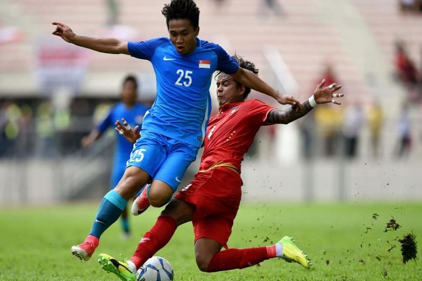 Myanmar defender Thiha Htet Aung tackling Young Lions defender Muhamad Rusyaidi during their Group A football match at the KL Games.