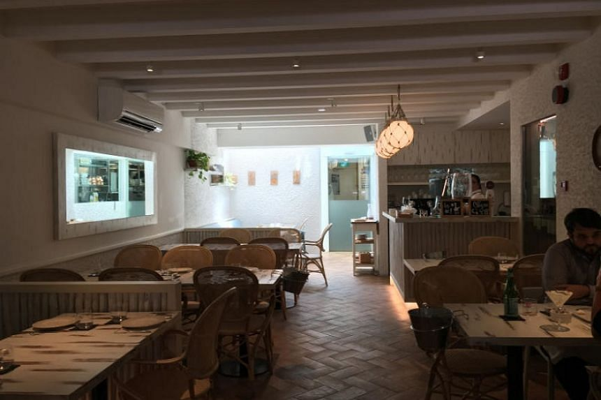 The interior of Restaurant Gaig has touches of Spain – textured white walls decorated with ornamental plates, dainty dinner dishes that look like porcelain doilies.