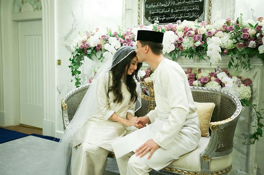 Dennis Muhammad Abdullah kissing the forehead of Johor Princess Tunku Tun Aminah Sultan Ibrahim, during their marriage ceremony at Istana Bukit Serene on Aug 14, 2017.