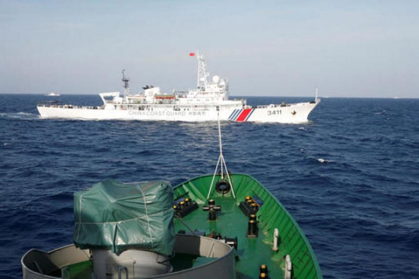 A ship (top) of the Chinese Coast Guard is seen near a ship of the Vietnam Marine Guard in the South China Sea on May 14, 2017.
