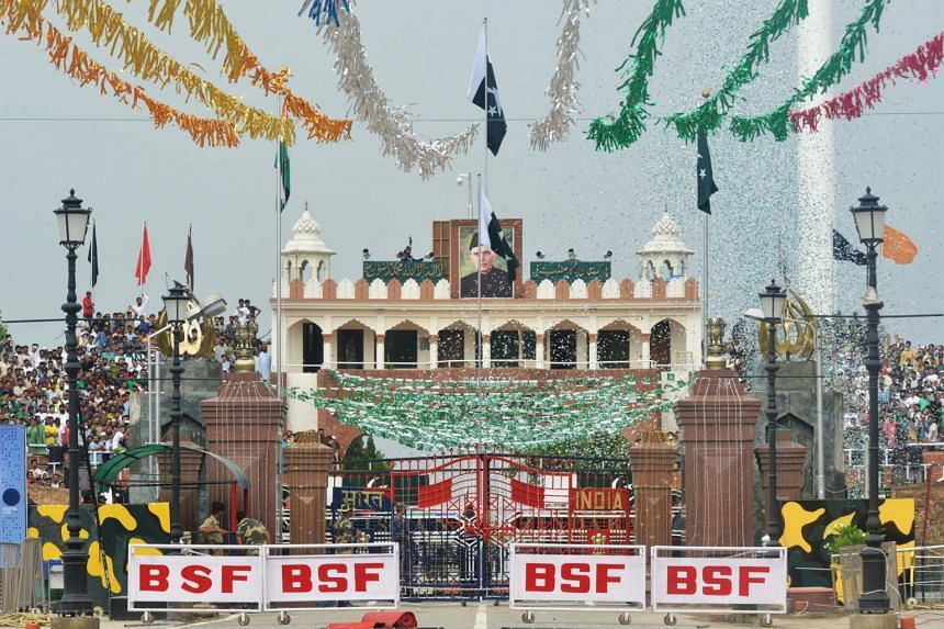 The Pakistani national flag is unfurled as people watch a ceremony celebrating the nation's Independence Day at the India-Pakistan Wagah border post on Aug 14, 2017.