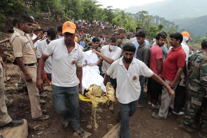 Indian rescuers remove the body of a victim after a landslide along a highway at Kotrupi on August 13, 2017.