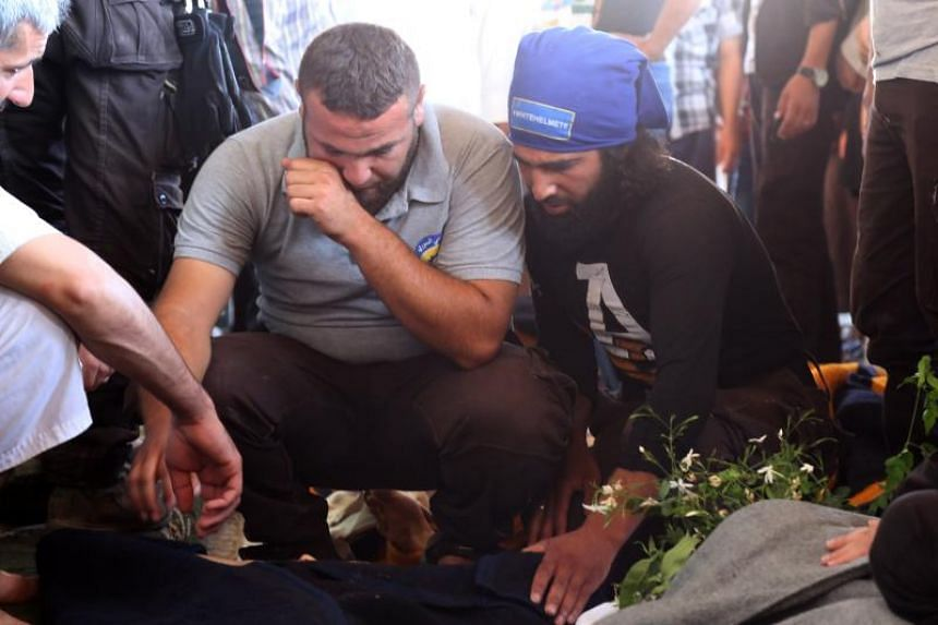 Mourners weep at the funeral for murdered members of the White Helmets on Aug 13, 2017.