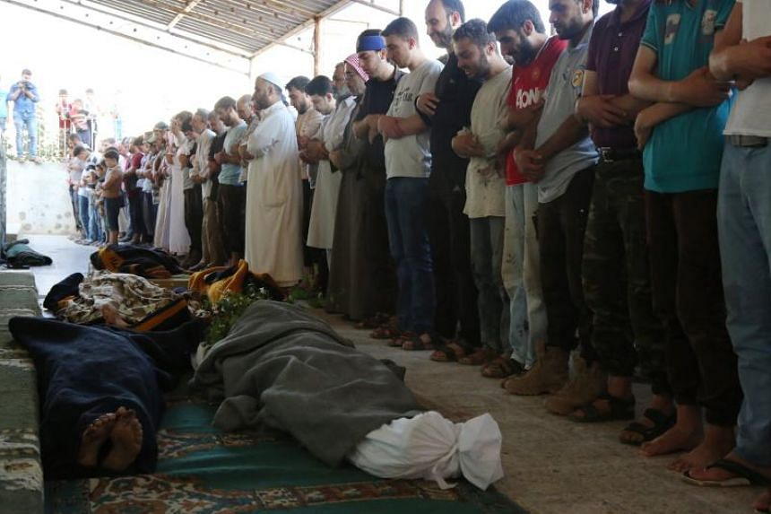 Mourners hold a funeral for members of the White Helmets rescue group who were shot dead at the office's of the group in the city of Sarmin in northwestern Syria on Aug 12,  2017.