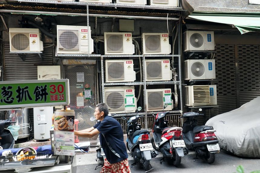 Air conditioning units hang from the exterior wall of a building in Taipei, Taiwan, on Aug 13, 2017.