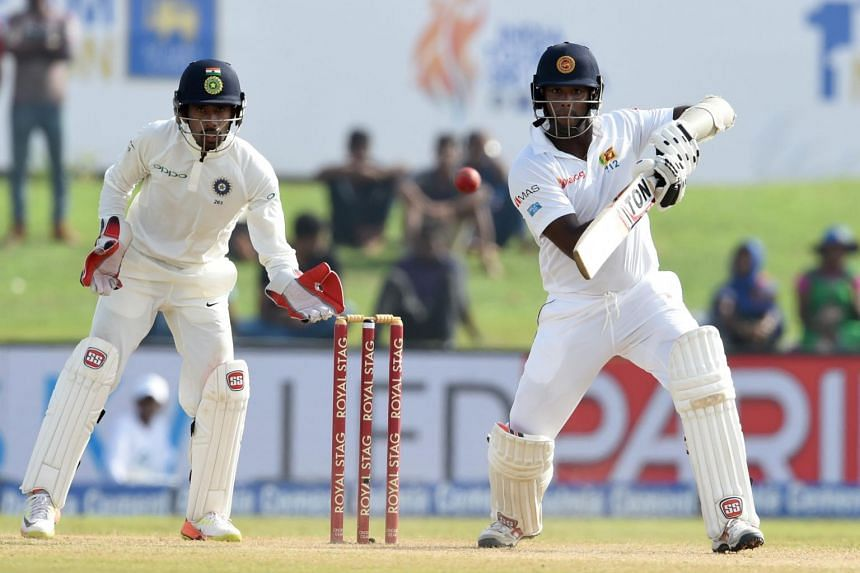 Sri Lankan batsman Angelo Mathews (right) plays a shot as Indian wicketkeeper Wriddhiman Saha looks on during the second day of the first Test match between Sri Lanka and India at Galle International Cricket Stadium in Galle on July 27, 2017.