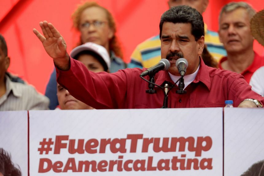 """Venezuela's President Nicolas Maduro stands next to a sign that reads """"Trump go away from Latin America"""" at a rally on Aug 14, 2017."""