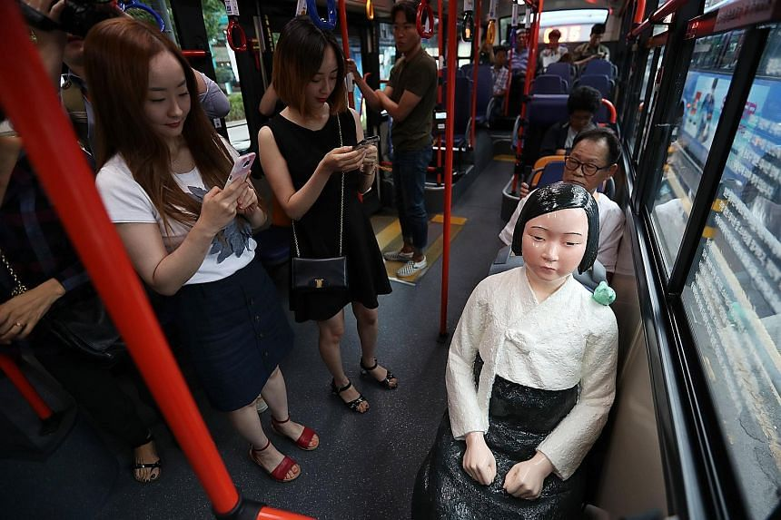 Passengers taking photos of a comfort woman statue installed on a city bus in Seoul yesterday, during the International Memorial Day for Comfort Women. A bus operator installed five comfort women statues on board its buses, and they are slated to rem
