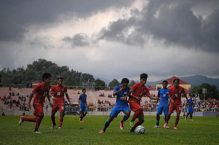 Under a stormy sky, Muhaiman Suhaimi (No. 7) attempts to gain possession during the 2-0 defeat by Myanmar at the Selayang Stadium yesterday. The Young Lions now face a crunch match against hosts Malaysia.