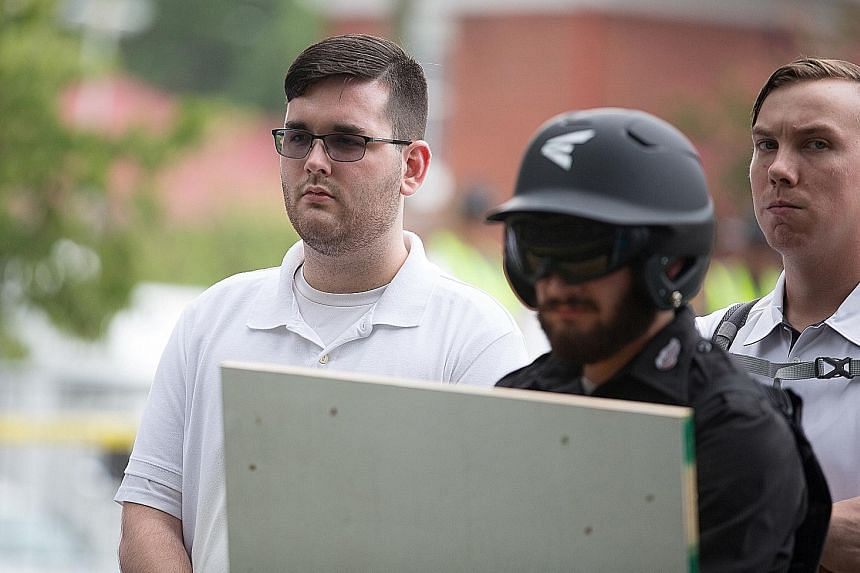 "James Alex Fields Jr (far left) attending the ""Unite the Right"" rally in Emancipation Park in Virginia last Saturday, before he drove a car into a crowd later that day, killing one person and injuring 19 others."