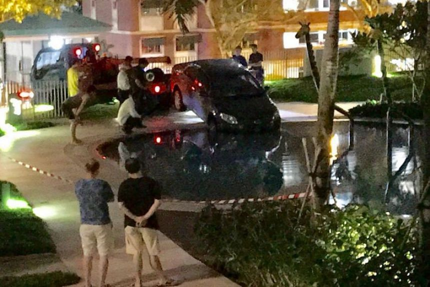The car was driven into the condominium pool on Aug 8. A male suspect is still missing. PHOTO: STOMP