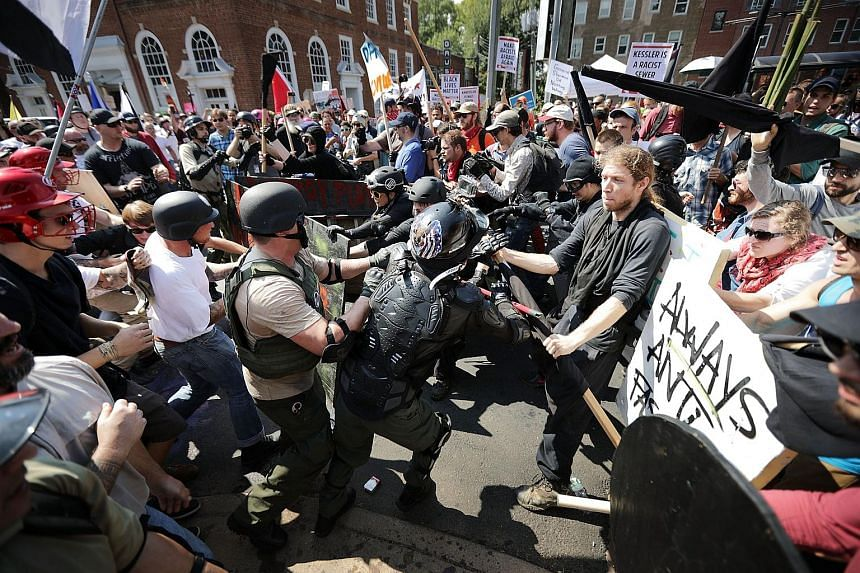 White nationalists clash with counter-protesters as they enter Lee Park during the Unite the Right rally on Aug 12, 2017.