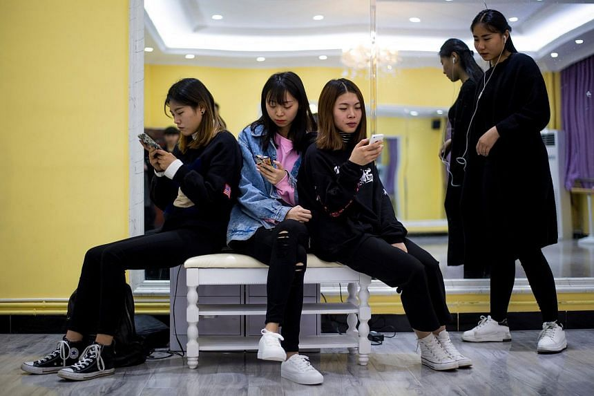 Students looking at their smartphones during a class at the Yiwu Industrial & Commercial College on March 14, 2017.
