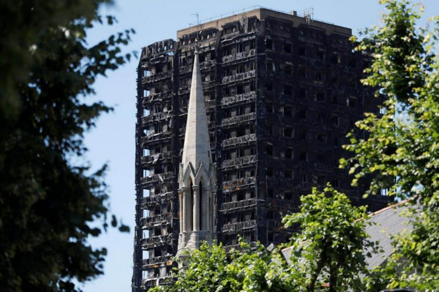 The spire of the Notting Hill Methodist Church stands in front of Grenfell Tower, destroyed in a catastrophic fire, in the Royal Borough of Kensington and Chelsea, in London, Britain.