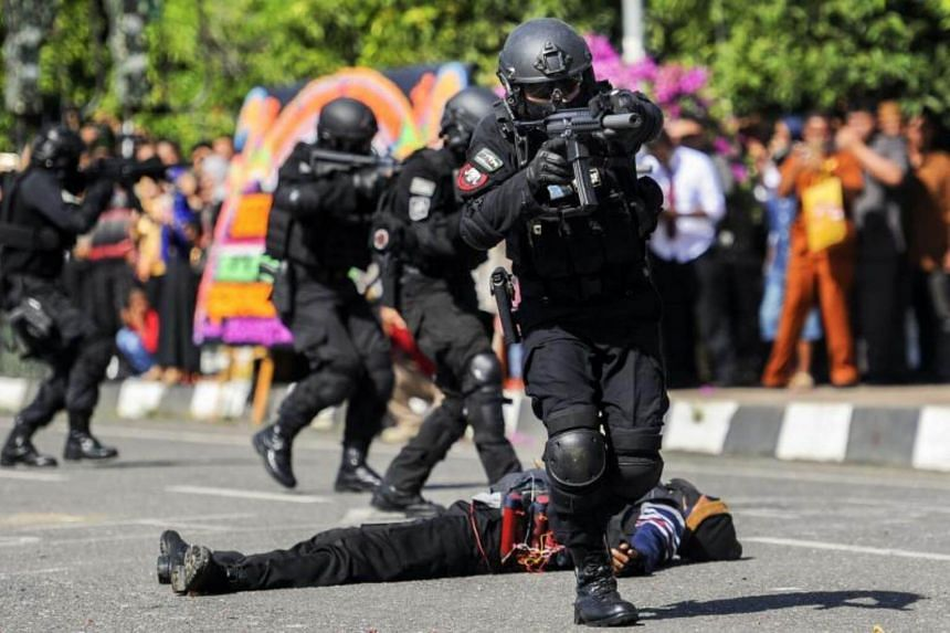 Police from the anti-terror squad participate in an anti-terror performance in Banda Aceh on July 10, 2017.