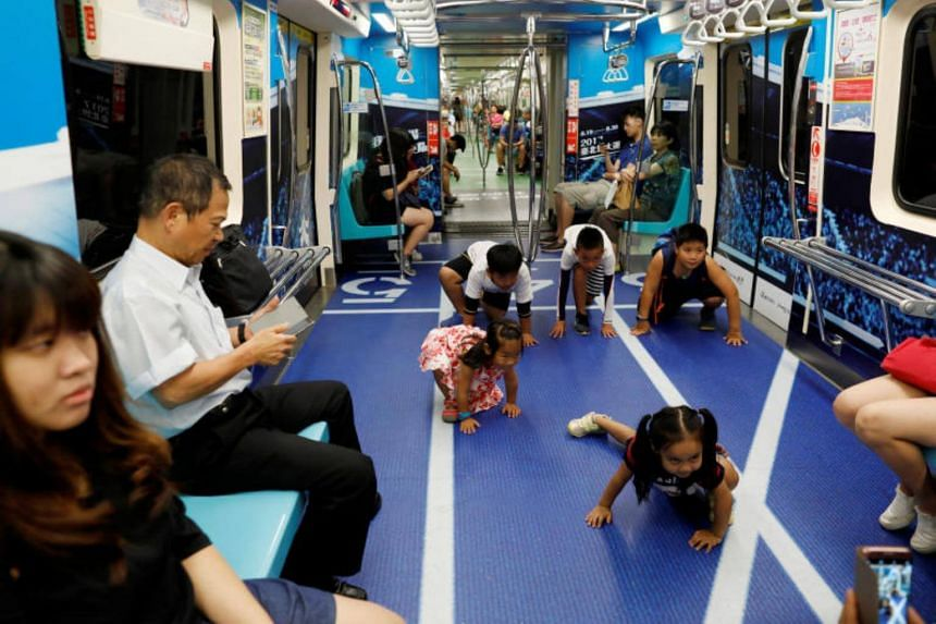 Children pose for photo at a sports-themed Mass Rapid Transit (MRT) train ahead of Summer Universiade, in Taipei, Taiwan on Aug 1, 2017.