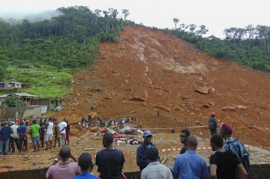 Residents view damage caused by a mudslide in the suburb of Regent behind Guma reservoir, Freetown, Sierra Leone on August 14, 2017.