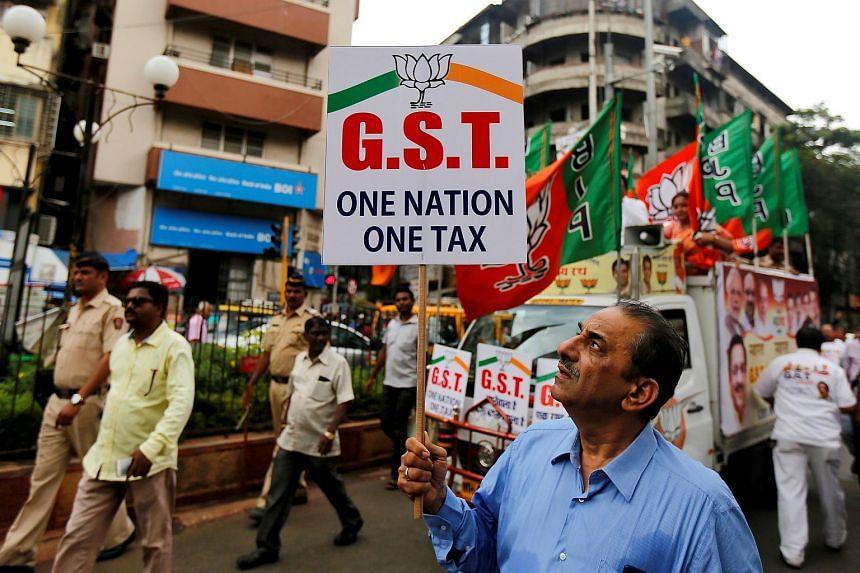 A man holding a placard during a rally to support implementation of the Goods and Services Tax (GST) in Mumbai, India, on June 30, 2017.