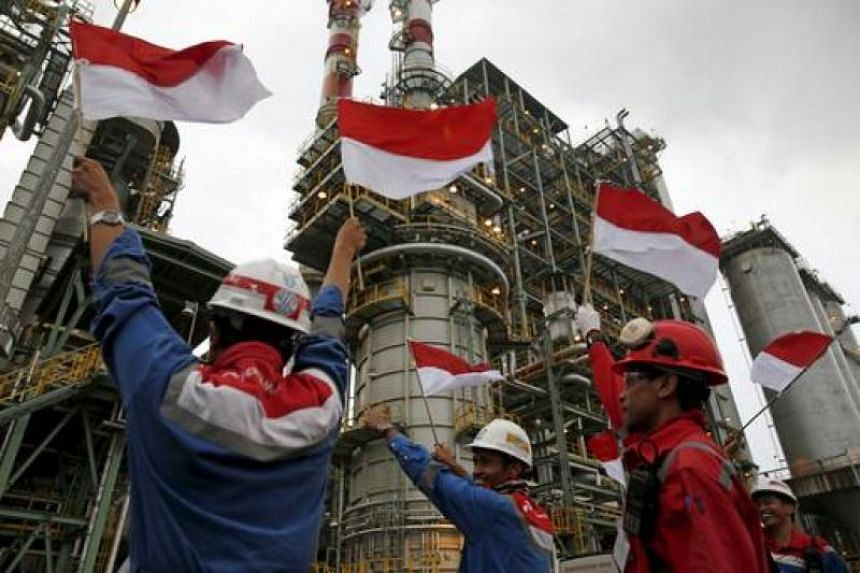 Pertamina employees wave Indonesian flags during a visit by the company's CEO Dwi Soetjipto and Indonesia's Vice-President Jusuf Kalla to the refinery unit IV in Cilicap, Central Java, Indonesia, on November 26, 2015.