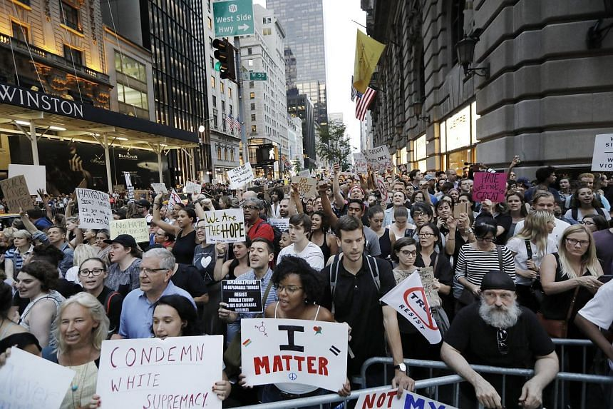 Protesters chant and hold up signs outside of Trump Tower in New York, on Aug 14, 2017.