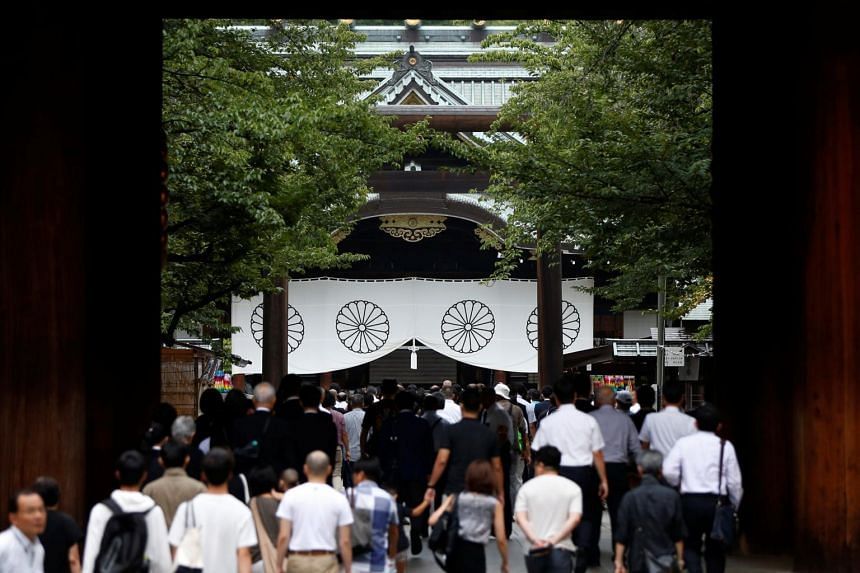 Visitors walking to the main shrine as they pay tribute to the war dead at Yasukuni Shrine in Tokyo, Japan, on Aug 15, 2017.
