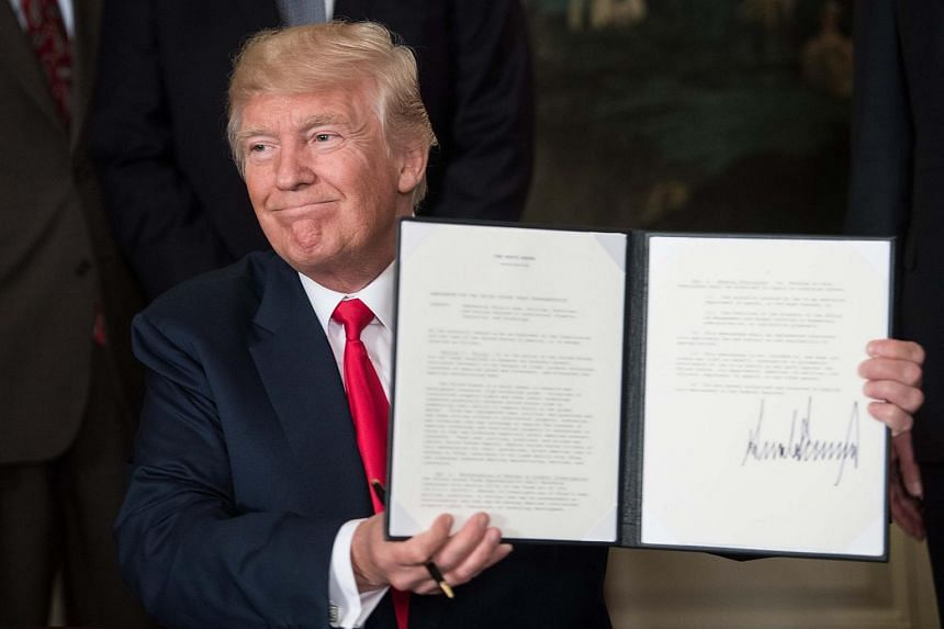 US President Donald Trump displays a memorandum on addressing China's laws, policies, practices, and actions related to intellectual property, innovation, and technology on Aug 14, 2017.