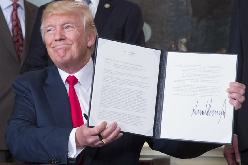 US President Donald Trump holds a signed memorandum addressing China's laws, policies, practices, and actions related to intellectual property at the White House on Monday, Aug 14, 2017.