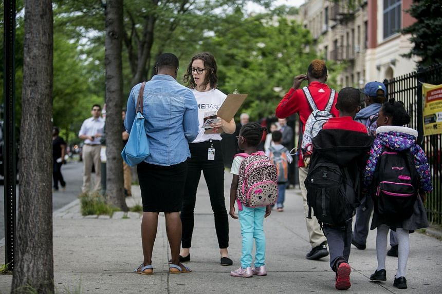 Ms Amelia Watts of New York City's Human Resources Administration, talking to a parent outside of a school in Brooklyn as part of a programme aimed at preventing families from becoming homeless, on June 16, 2017.