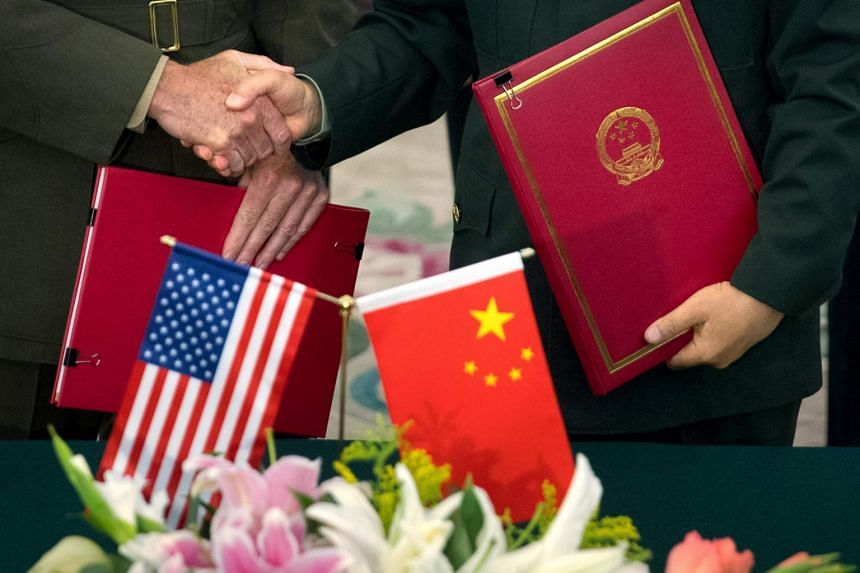General Joseph Dunford (left), chairman of the US Joint Chiefs of Staff, and Chief of the General Staff of the Chinese People's Liberation Army General Fang Fenghui shake hands after signing an agreement at the Bayi Building in Beijing on Aug 15, 201